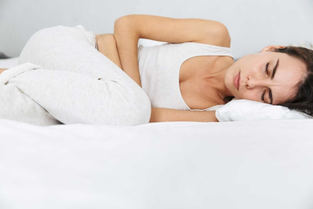 Femme couché maux de ventre